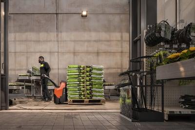 transpaleta eléctrica con conductor acompañante transportando sacos de tierra